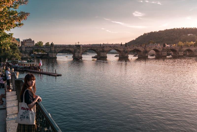 Prague Tjeckien - September 10, 2019: Ungt asiatiskt kvinnaanseende bredvid den Vltava floden under solnedgången med arkivfoto