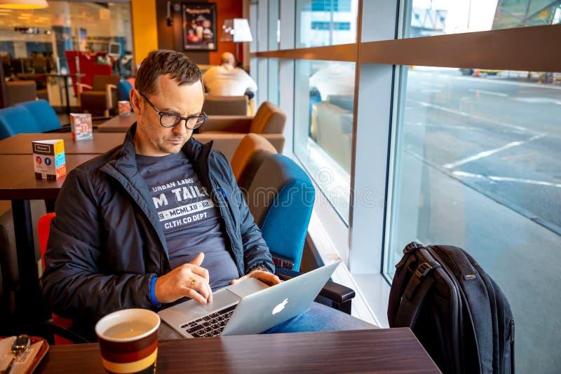 Prague Tjeckien - 01 02 2019: Stilig man som sitter på tabellen och arbetar på bärbara datorn i Prague flygplatskafé arkivbilder
