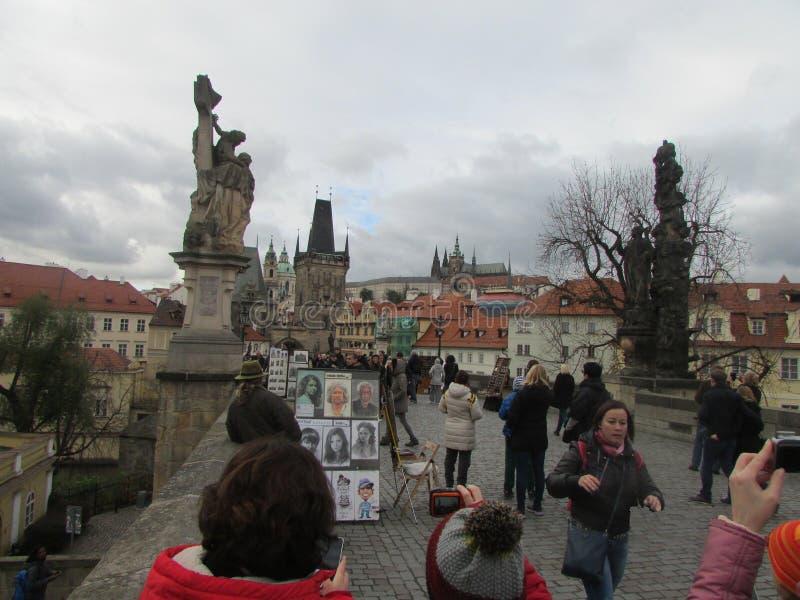 Prague Tjeckien, turister på Charles Bridge, konstnären, statyerna av konungar royaltyfria bilder
