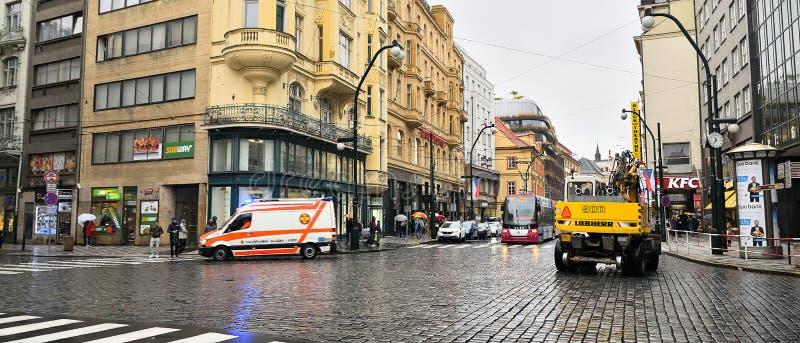 Praha, Tsjechische republiek - 28 Oktober, 2018: ziekenwagen, graafwerktuig en tram in Narodni-straat in dag van eeuwfeest van he stock foto's