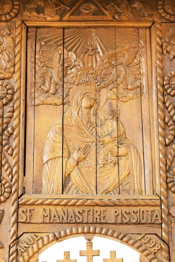 Prahova, Romênia - 30 de março de 2019: Ícone de madeira cinzelado da Virgem Maria e do bebê Jesus no monastério de Pisiota situa fotografia de stock