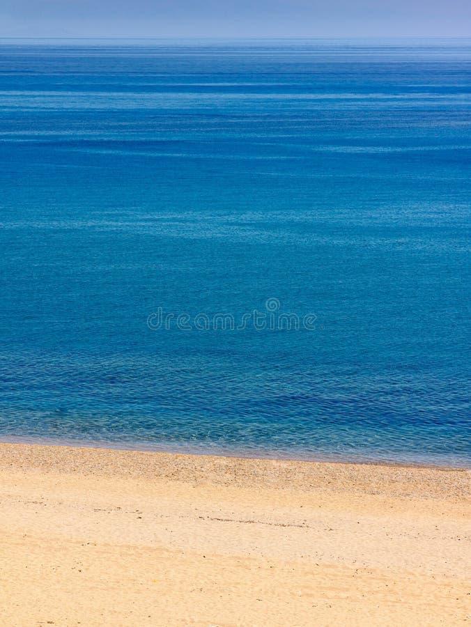 Praia Abandonada Com O Mar Azul Brilhante Foto de Stock Royalty Free
