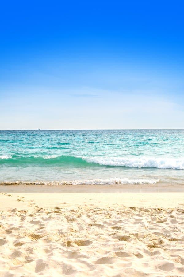 Praia arenosa bonita de encontro ao céu azul fotos de stock