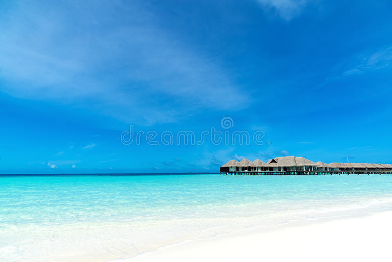 Praia bonita com os bungalows da água em Maldivas fotos de stock