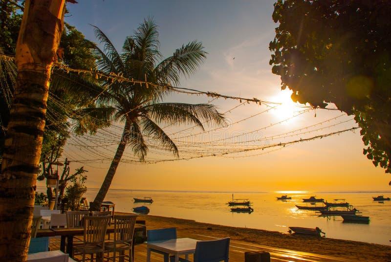 Praia bonita com um café em Sanur com as palmeiras tradicionais locais dos barcos na ilha de Bali no alvorecer indonésia fotos de stock