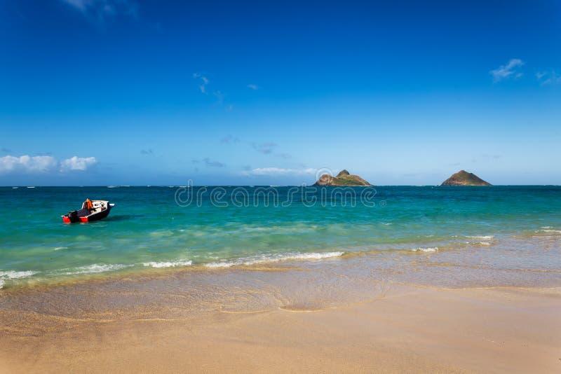 Praia bonita de Lanikai com água de turquesa e um barco de motor fotos de stock