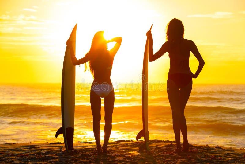 Praia bonita do por do sol das prancha das meninas das mulheres do surfista do biquini imagens de stock