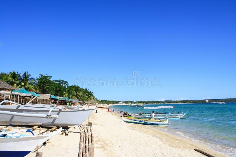 Praia branca da areia com o céu azul, águas e os barcos de turista claros fotografia de stock royalty free
