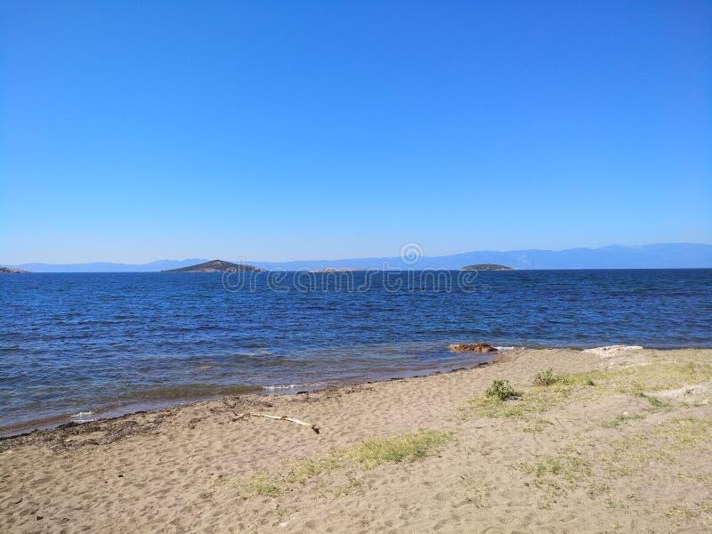 Praia clara do céu azul imagens de stock