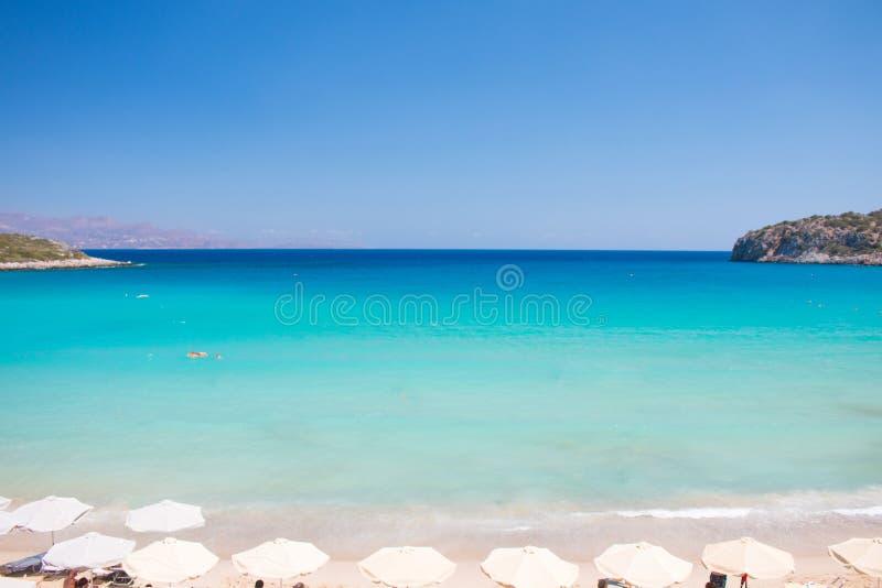 Praia colorida bonita na ilha da Creta, Grécia Praia do paraíso de Voulisma com guarda-chuva e sunbeds Holid do curso das férias  imagem de stock royalty free