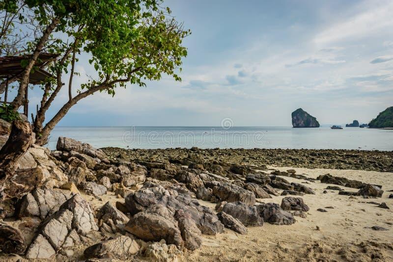 Praia com areia e pedras na área de Krabi, árvore com as folhas verdes à esquerda, ilha tailandesa no fundo, navio pequeno, céu a imagem de stock