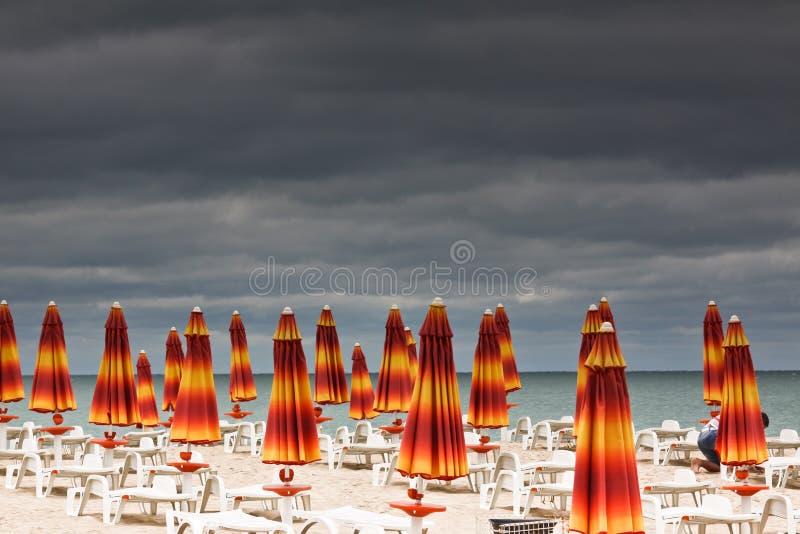 Praia com deckchairs e mar dos parasóis fotos de stock royalty free