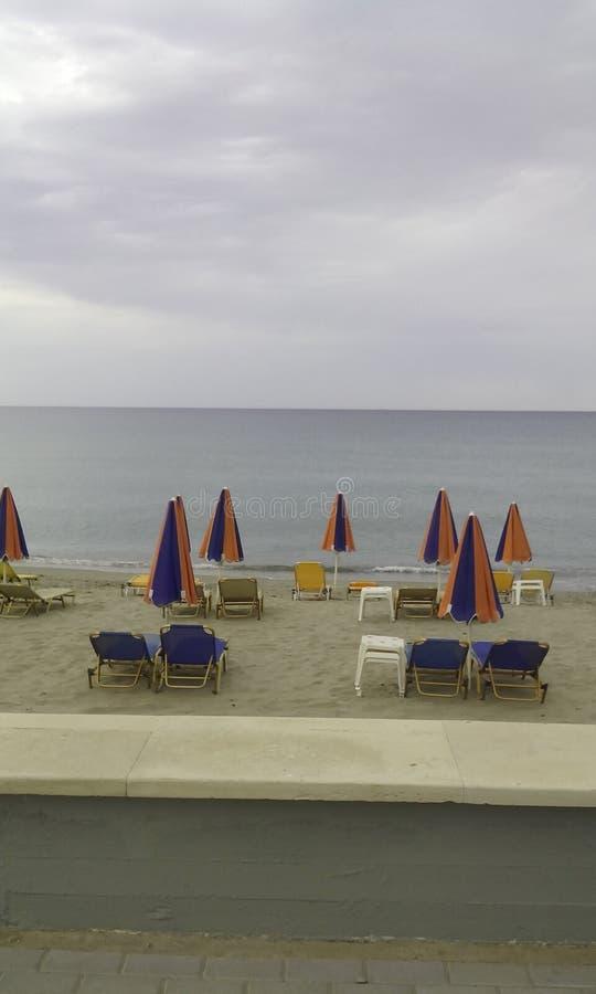 Praia com guarda-chuvas, cadeiras de plataforma e horizonte imagem de stock