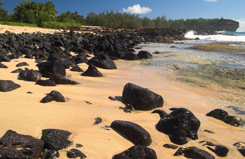 Praia com os pedregulhos vulcânicos traseiros, Kauai do naufrágio fotografia de stock royalty free