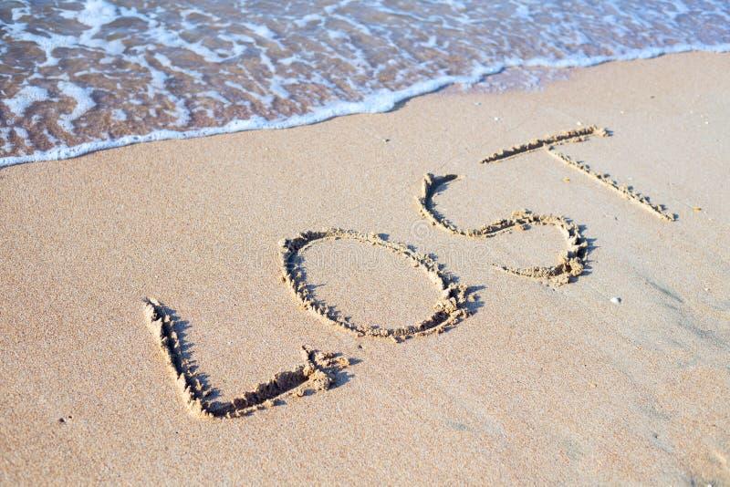 Praia com palavra da areia perdida imagem de stock