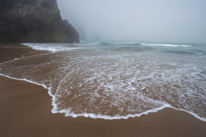 Praia da Adraga beach - White ocean waves and silhouette of costal rocks in morning fog. Sintra, Portugal stock photography