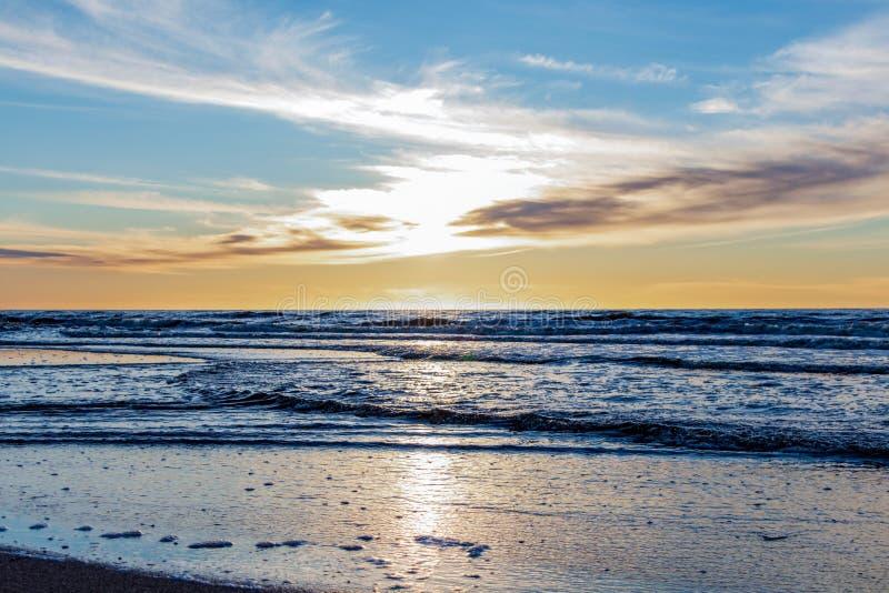 Praia da areia com horizonte infinito e ondas espumosas sob o p?r do sol brilhante com cores amarelas e nuvens acima do mar fotografia de stock royalty free