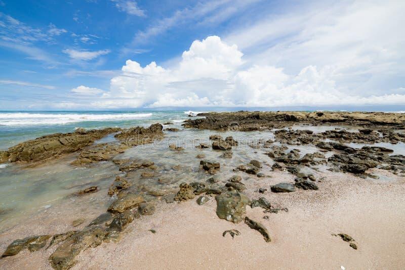 Praia da areia das ondas e dia ensolarado das nuvens imagem de stock