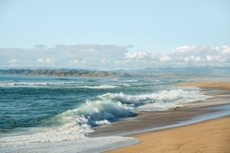 Praia da areia, ondas que quebram à costa, montanhas, e céu azul nebuloso fotos de stock