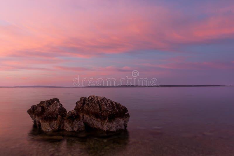 Praia da Croácia do nascer do sol com cor pastel e rocha no primeiro plano fotografia de stock royalty free