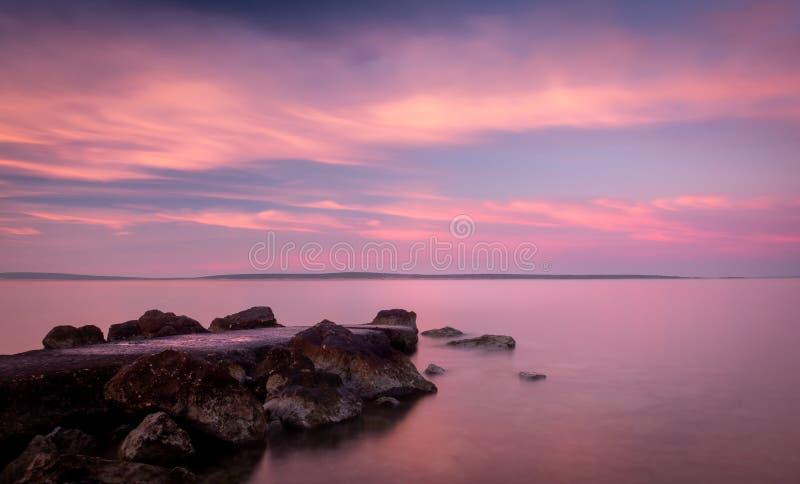 Praia da Croácia do nascer do sol com cor pastel Rocky Jetty imagens de stock royalty free