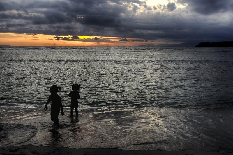 A praia da noite, pessoa tem o divertimento no oceano no por do sol fotos de stock