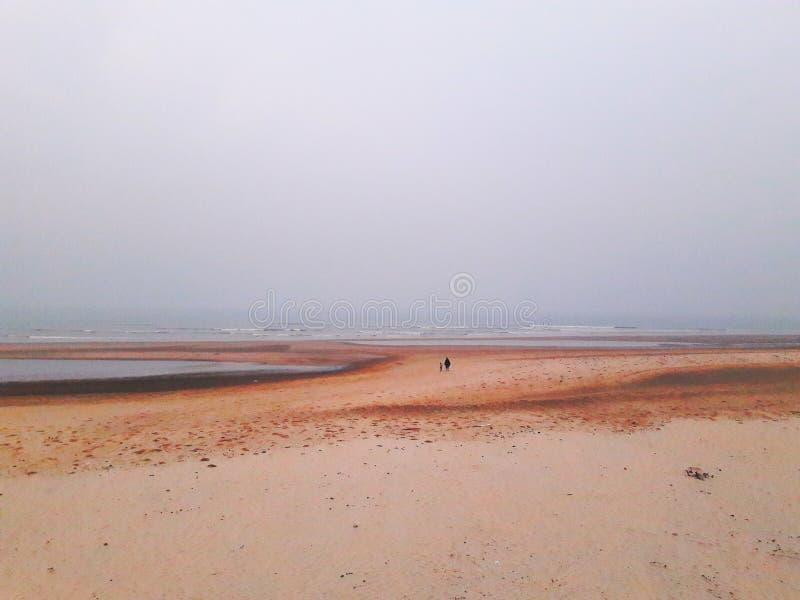 Praia de areia de Puri, Índia com um horizonte largo e uma pessoa com uma criança a andar para longe imagens de stock