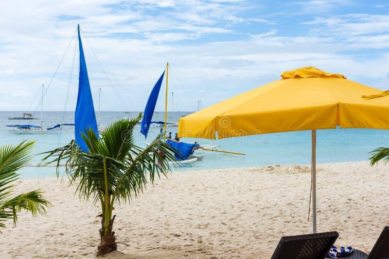 Praia de Boracay, palmeiras pequenas e um parasol amarelo foto de stock