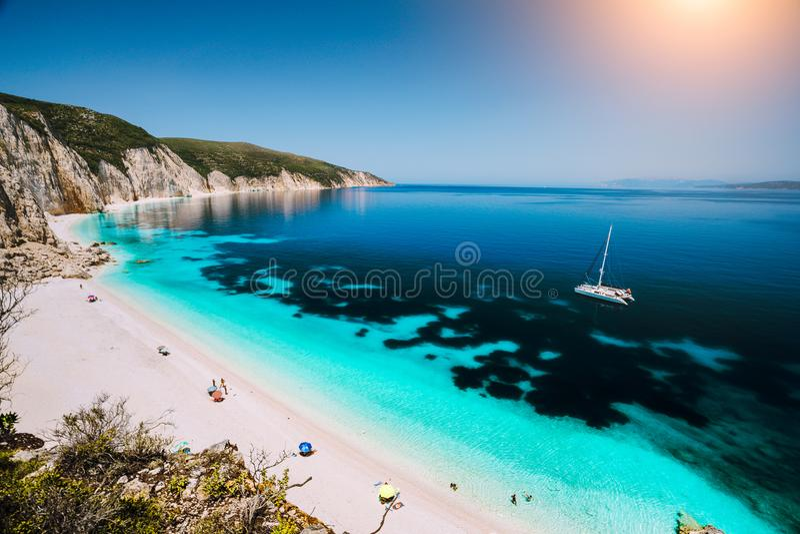 Praia de Fteri, Cephalonia Kefalonia, Grécia Iate branco do catamarã na água do mar azul clara Turistas no Sandy Beach próximo imagem de stock royalty free
