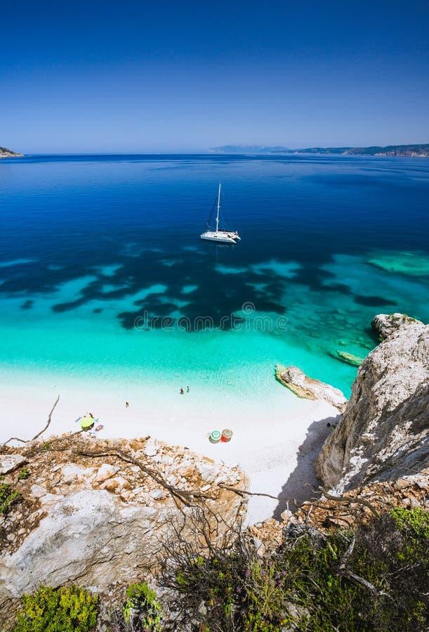 Praia de Fteri, Cephalonia Kefalonia, Grécia Iate branco do catamarã na água do mar azul clara Turistas no Sandy Beach próximo fotos de stock royalty free