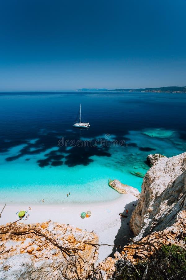 Praia de Fteri, Cephalonia Kefalonia, Grécia Iate branco do catamarã na água do mar azul clara Turistas no Sandy Beach próximo imagens de stock royalty free