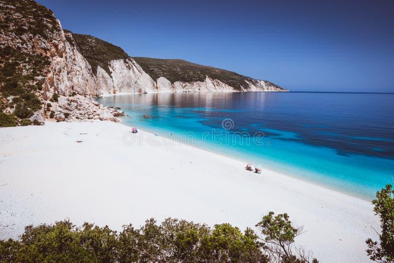 Praia de Fteri, Kefalonia, Grécia Os turistas sós protegidos do frio do guarda-chuva de sol relaxam perto da esmeralda azul clara imagens de stock