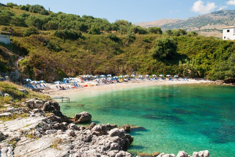 Praia de Kassiopi, ilha de Corfu, Grécia Sunbeds e parasóis (sol imagens de stock