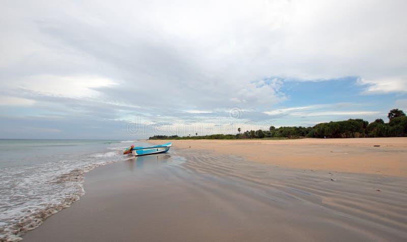 Praia de Nivali com barco e testes padrões listrados da areia em Trincomalee Sri Lanka foto de stock royalty free