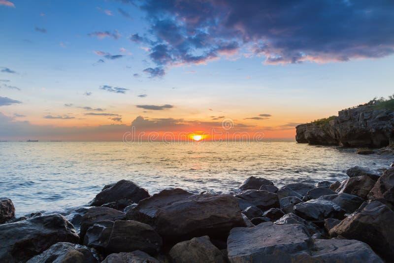 Praia de pedra sobre o litoral com o céu bonito do por do sol imagens de stock