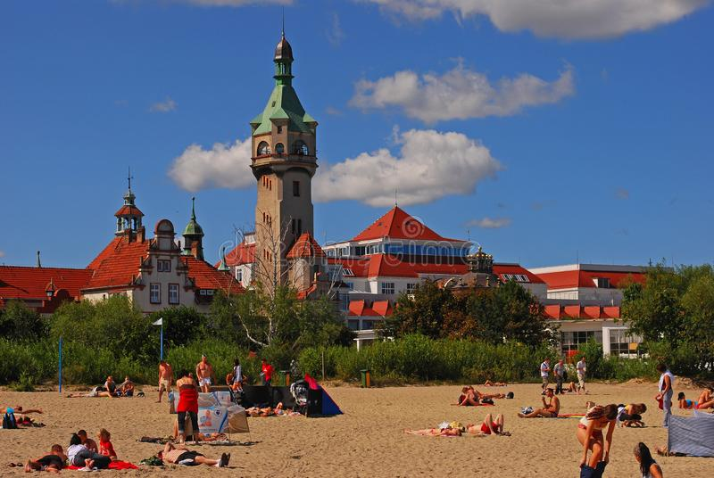 Praia de Sopot, situada ao norte do Polônia com o farol velho no fundo com os visitantes que tomam sol apreciando o dia imagens de stock
