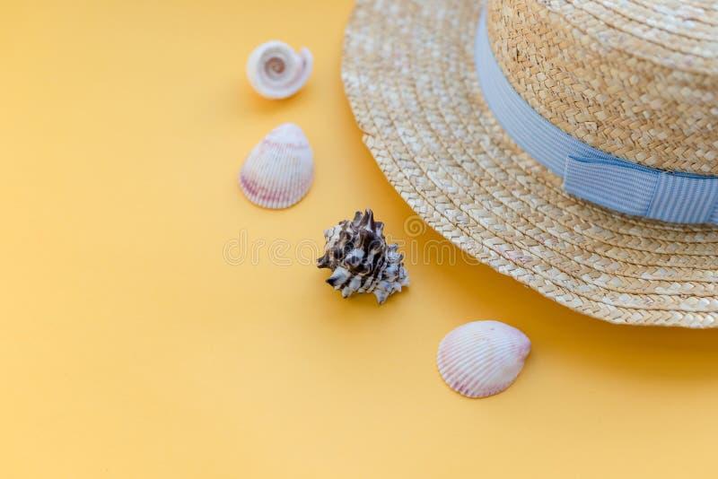 Praia do chapéu de palha do verão com as conchas do mar no fundo amarelo Acess?rios do ver?o E Conceito para fotografia de stock