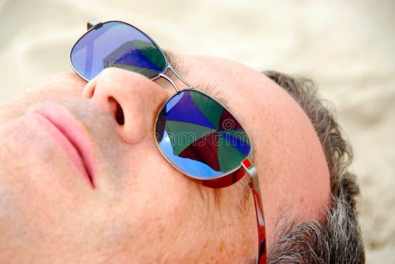 A praia do homem relaxa imagem de stock