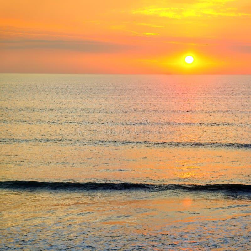 Praia do oceano e do nascer do sol vermelho foto de stock