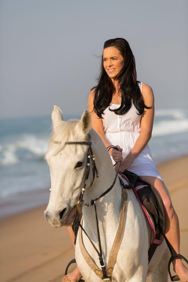 Praia do passeio do cavalo da mulher fotografia de stock