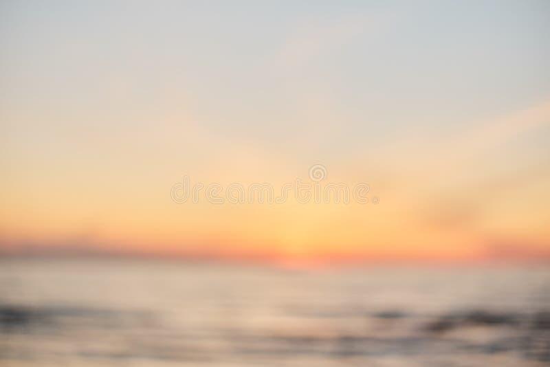 Praia do por do sol do borrão com fundo do sumário da onda clara do bokeh fotos de stock
