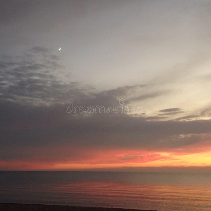 Praia e céu do por do sol fotografia de stock