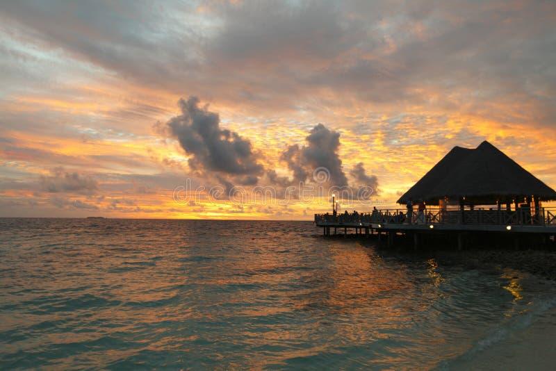 Praia e casas tropicais no por do sol imagem de stock royalty free