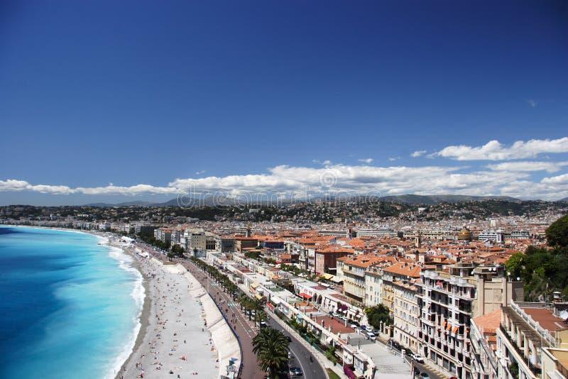 Praia e cidade agradáveis imagens de stock