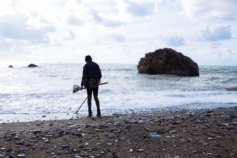 Praia e homem com detector de metais Foto 2018 do curso, dezembro fotos de stock