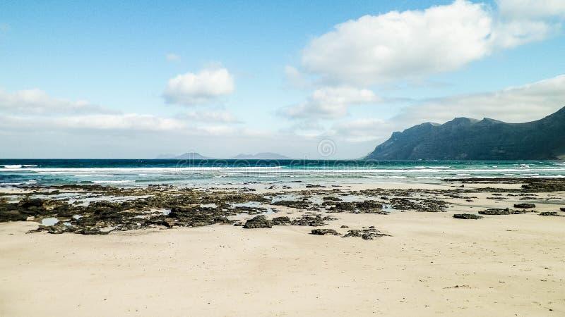 Praia e montanhas - costa bonita em Caleta de Famara, Ilhas Canárias de Lanzarote fotos de stock