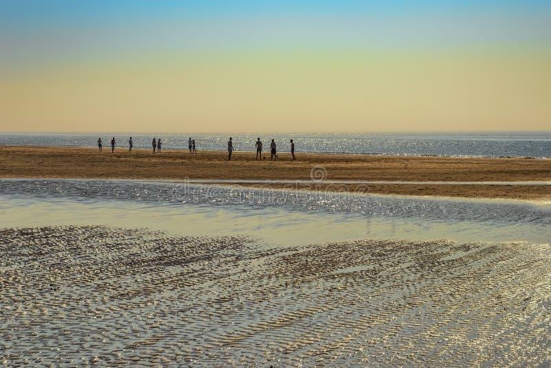 A praia e o mar na maré alta no sol de ajuste na vila holandesa norte de Castricum pelo mar na distância lá AR fotos de stock royalty free