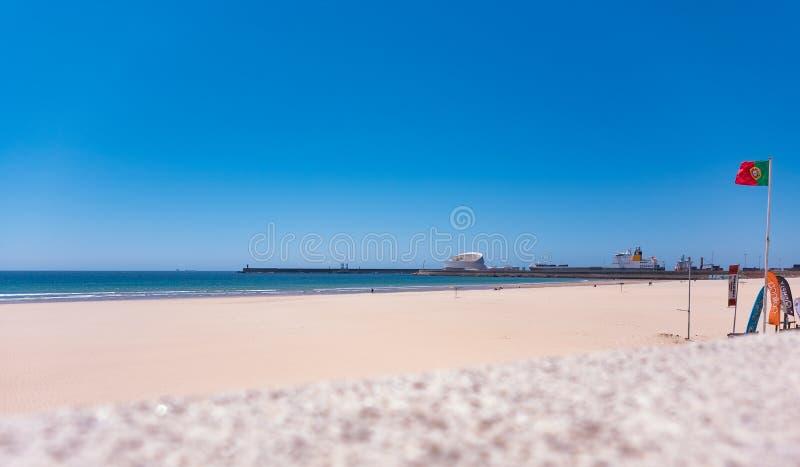 Praia em Matosinhos, Porto, Portugal com a parede no primeiro plano e a bandeira portuguesa no direito fotografia de stock