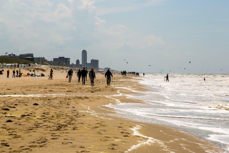 Praia em Zandvoort, Países Baixos Povos do grupo que andam junto ao longo da praia imagens de stock