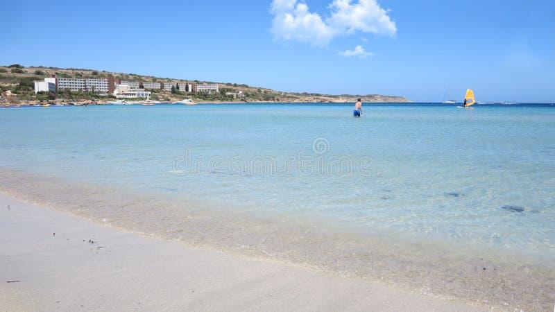 Praia ensolarada com água claro imagem de stock